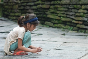 Little girl playing marbles in Nepal
